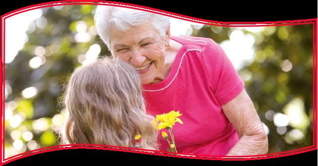 Fröhliche ältere Dame und ihre Enkelin freuen sich über eine Blume