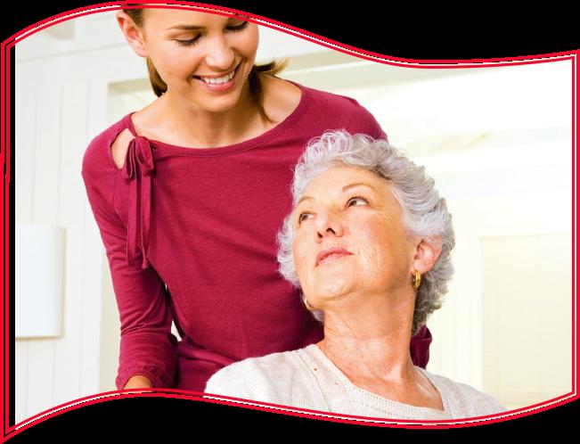 Freundliche Pflegerin schiebt ältere Dame im Rollstuhl
